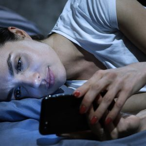 Woman unable to sleep, looking at phone in bed.